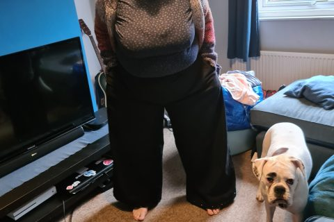 woman wearing black trousers with pockets. white boxer dog in foreground